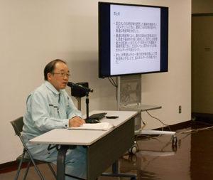 ディスプレイの横で発表をしている男の人の写真1